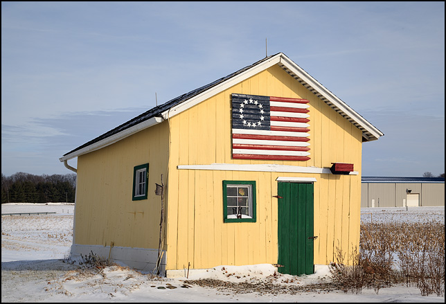A yellow storage shed with a thirteen star American flag painted on a piece of wooden fence mounted over the door. The shed sits behind a house on US-33 in the small town of Merriam, Indiana.