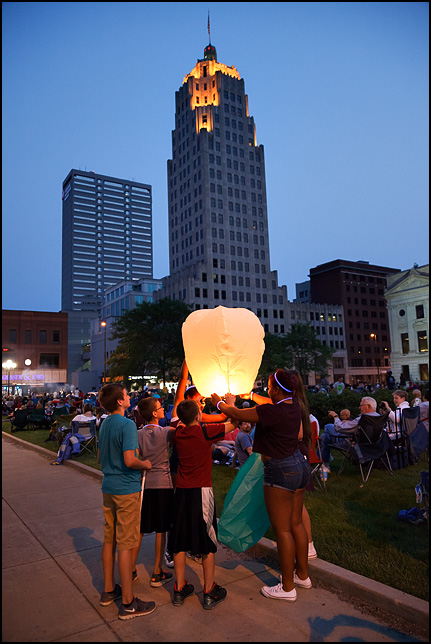 A group of teenagers holding a sky lantern hot-air balloon before the Fourth of July Fireworks on the Courthouse Green in downtown Fort Wayne, Indiana.