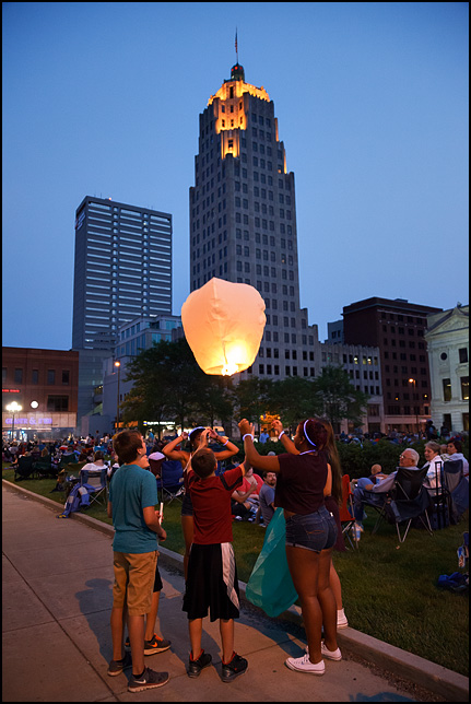 A group of teenagers launching a sky lantern hot-air balloon before the Fourth of July Fireworks on the Courthouse Green in downtown Fort Wayne, Indiana.