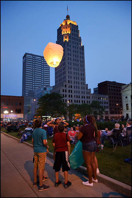 A group of teenagers watching the flight of a sky lantern hot-air balloon before the Fourth of July Fireworks on the Courthouse Green in downtown Fort Wayne, Indiana.