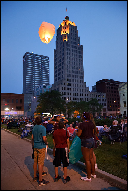 A group of teenagers watching  a sky lantern hot-air balloon fly past the Lincoln Tower in downtown Fort Wayne, Indiana.