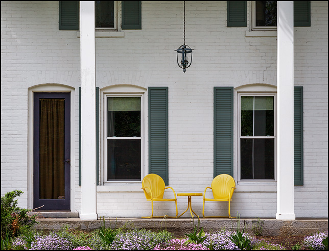 A pair of yellow motel chairs with a matching table sit under a hanging light on the front porch of a large old whitewashed brick house on Winchester Road in Fort Wayne, Indiana.