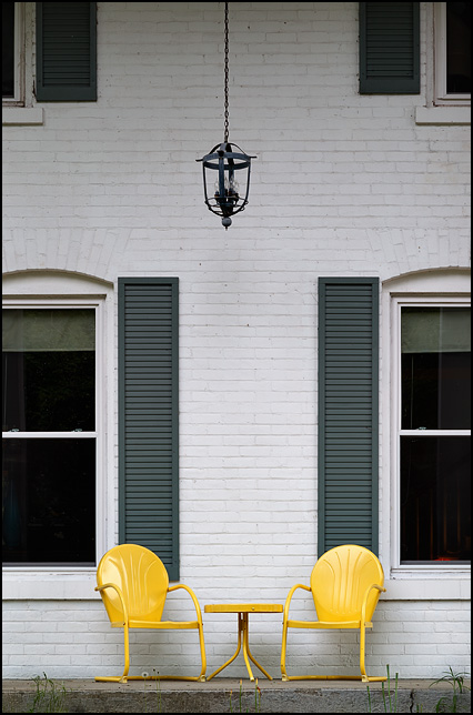 Two yellow metal shellback chairs and a matching table sit under a hanging light on the front porch of a 19th Century brick farmhouse on Winchester Road in Fort Wayne, Indiana.