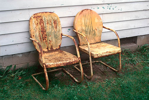 A pair of old rusty yellow metal motel chairs next to an old white house with peeling paint in rural southwest Allen County, Indiana. Photographed after a rainstorm.