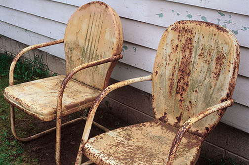 Two rusty old yellow metal motel chairs next to grandpas house.