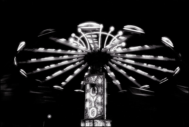 A brightly lit carnival ride called The Yo-Yo in motion at night.