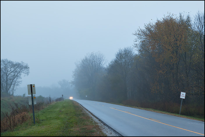Headlights coming out of the fog on a rainy evening at dusk on Yohne Road in southwest Allen County, Indiana.
