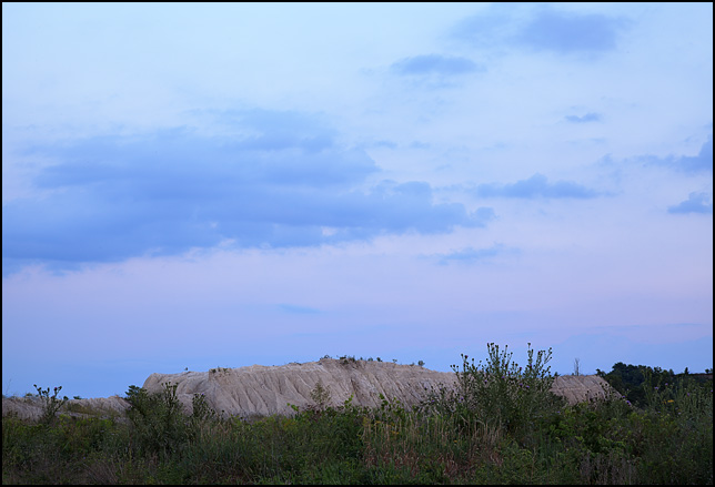A purple sunset sky over a mountain of limestone quarry overburden along Yohne Road in southwest Allen County, Indiana.