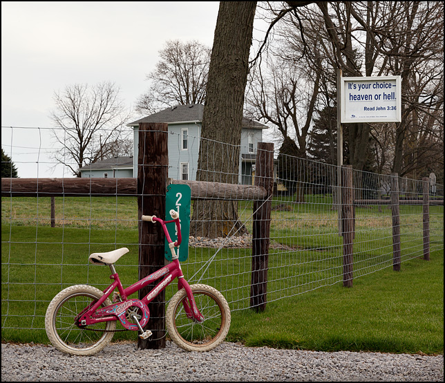 A religious sign on a fence post in front of a farmhouse on State Road 37 in rural northeast Allen County, Indiana. Its Your Choice - Heaven or Hell. Read John 3:36. A little girls bicycle is leaned against one of the fence posts.
