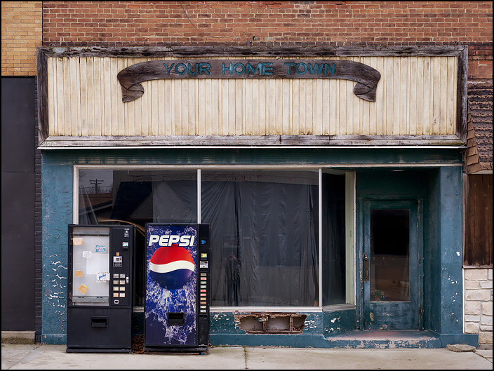 A vacant storefront on Main Street in the small town of Andrews, Indiana. the wooden banner across the front of the building says Your Home Town.