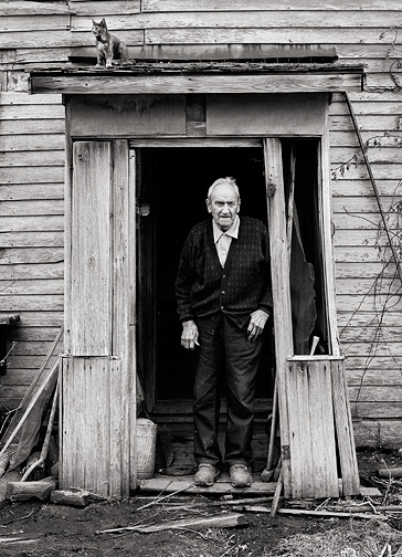 Elderly hoosier farmer Richard Youse standing in the doorway of his dilapidated farmhouse while one of his cats sits on the roof of the entryway.