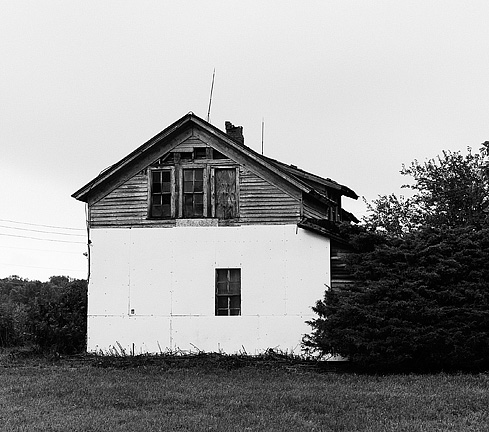 An abandoned farm house on Emenhiser Road in rural southeast Allen County, Indiana. The weathered wood siding is partly covered in styrofoam insulation and a very large evergreen bush grows in front of the old house and lightening rods stand atop the roof.