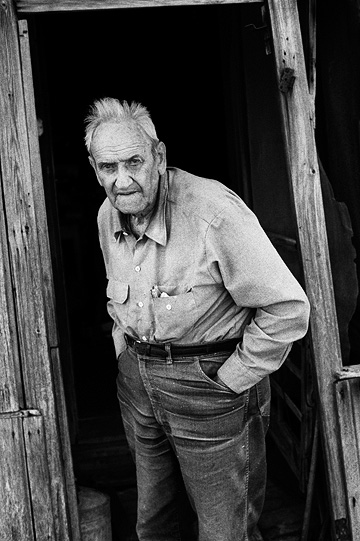 Elderly hoosier farmer Richard Youse standing in the doorway of his weathered old house in rural Allen County, Indiana.