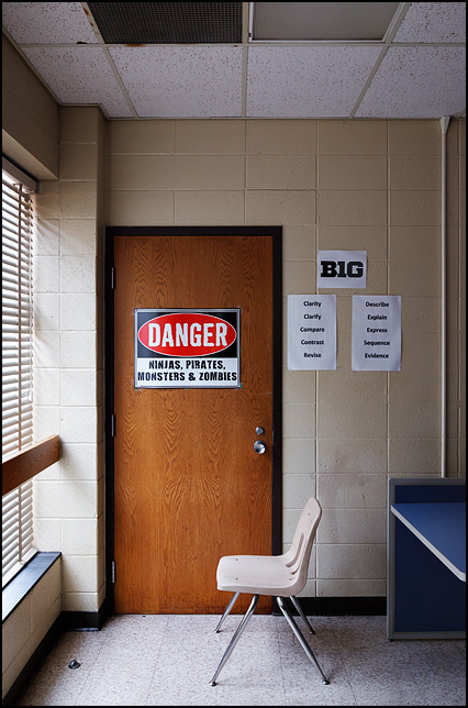 A warning sign on the door of a classroom in a middle school that says, Danger - Ninjas Pirates Monsters and Zombies.