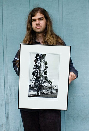 Fine art photographer christopher crawford holding a framed photograph of a carnival ride called the zipper